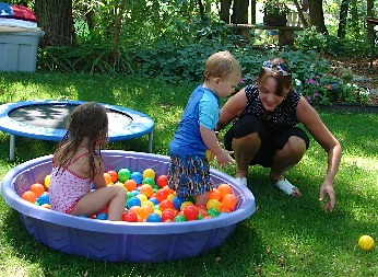 Kids playing in their ball pit outside