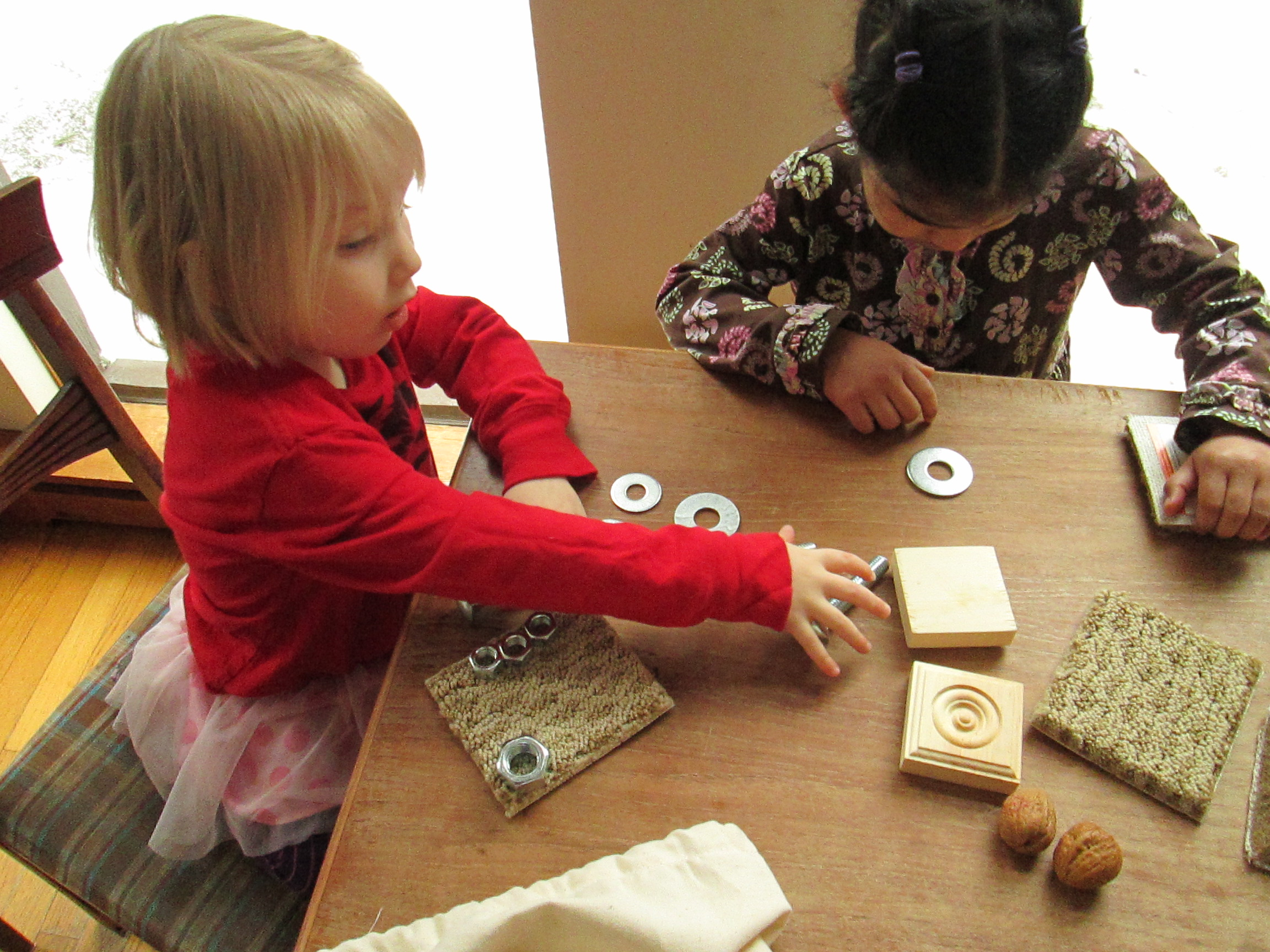 Two girls playing with comparing bag on tabletop