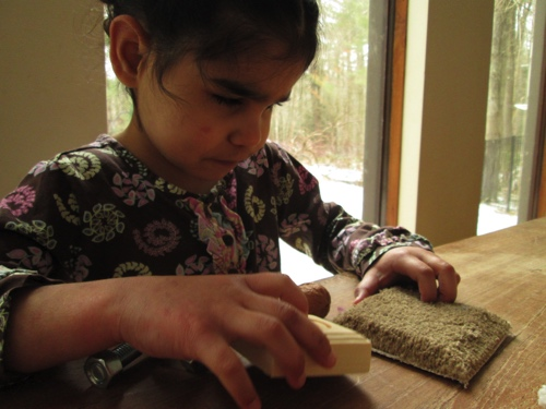 Anelia touching wood and carpet.