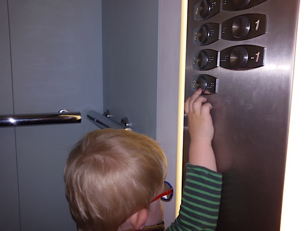 Enzo touching the buttons and the braille in an elevator