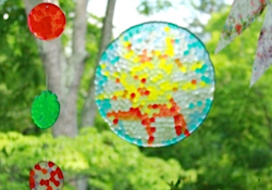 Four circle suncatchers with stained glass appearance hanging in the window
