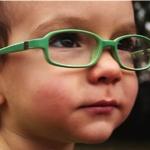little boy wearing green glasses