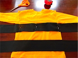 sewing the black stripes to the yellow shirt