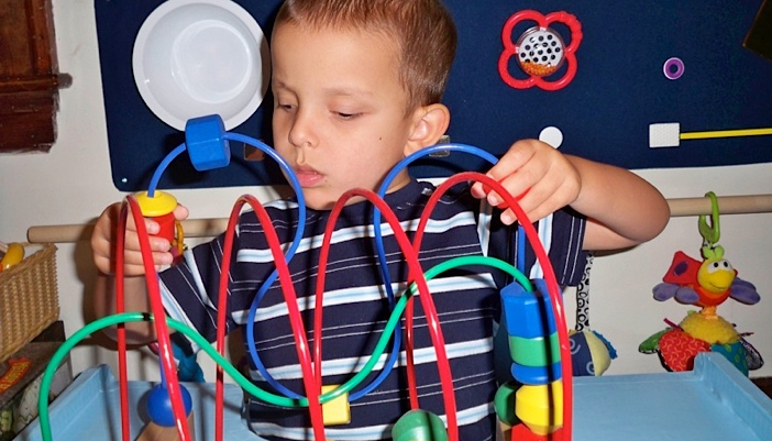 Ivan playing with his bead maze