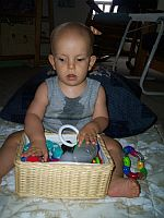Ivan feeling all the toys in his toy basket.