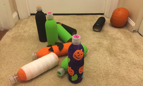 Bottle pins knocked over with pumpkin bowling ball
