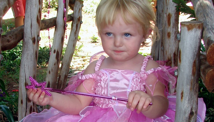 little girl in a pink dress with a magic wand