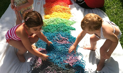 Kids playing with rainbow noodles