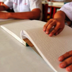 Students' hands reading braille books on a desk