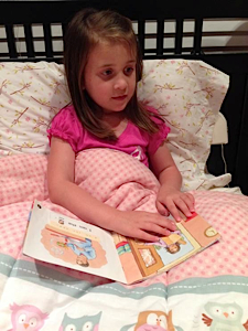 little girl reading braille in bed