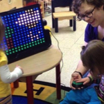 Kids in a preschool classroom gathered around the LightAide device