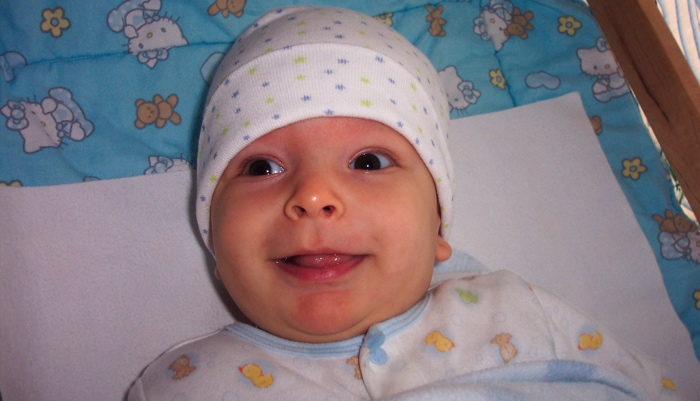 Baby Ivan smiling and wearing a hat