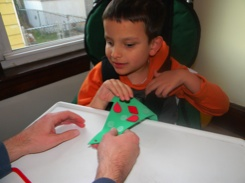 Ivan putting ornaments on our tactile Christmas tree craft