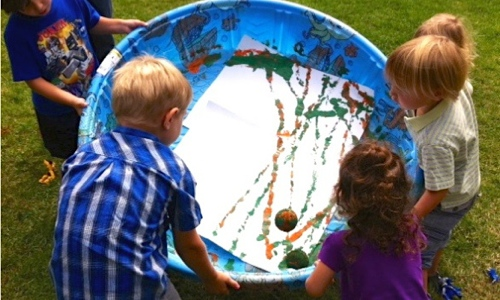 Kids using a tennis ball to paint on a large piece of paper in a kiddie pool