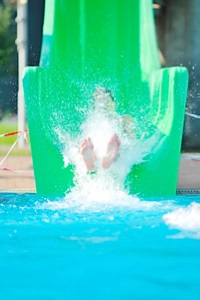 Little girl going down a water slide