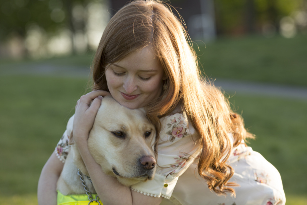 A young woman with red hair hugging her guide dog, a yellow lab