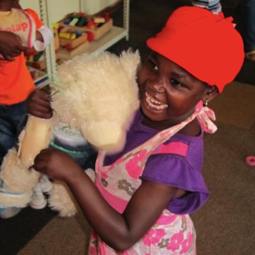 little girl hugging her Aware Bear