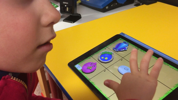 young girl using finger drag to explore the game grid on the iPad in the Ballyland coding app