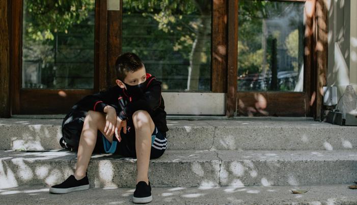 boy wearing a black mask outside school